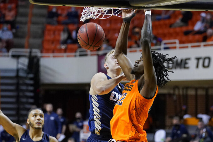 Oklahoma State forward Kalib Boone, right, dunks in front of Oral Roberts forward Francis Lacis, center, durikng the second half of an NCAA college basketball game Tuesday, Dec. 8, 2020, in Stillwater, Okla. (AP Photo/Sue Ogrocki)
