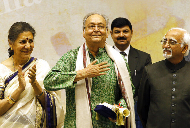 FILE- In this May 3, 2012 file photo, Bengali language film actor Soumitra Chatterjee, center, gestures after receiving the Dadasahab Phalke Award for the year 2011, as Indian Vice President Hamid Ansari, right, and Indian Minister for Information and Broadcasting Ambika Soni look on, during the 59th National Film Awards in New Delhi, India. Chatterjee, the legendary Indian actor with more than 200 movies to his name and famed for his work with Oscar-winning director Satyajit Ray, has died. He was 85. (AP Photo/ Manish Swarup, File)