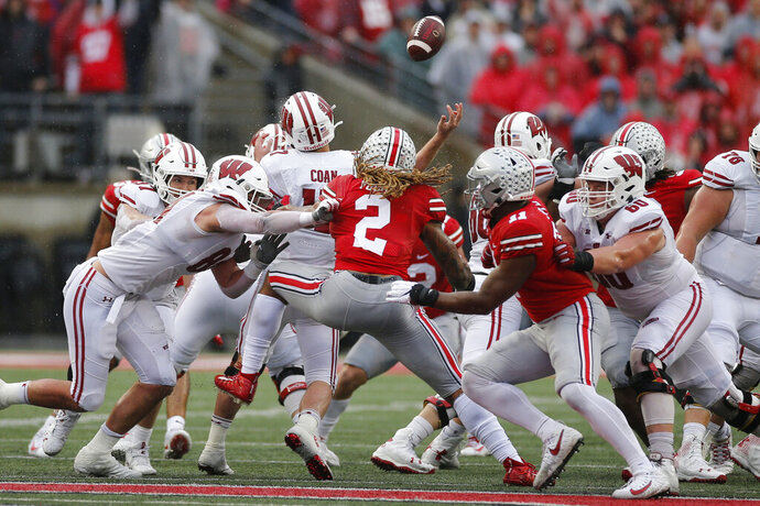 Ohio State defenders Chase Young (2) and Tyreke Smith (11) cause Wisconsin quarterback Jack Coan to fumble the ball on fourth down during the second half of an NCAA college football game Saturday, Oct. 26, 2019, in Columbus, Ohio. Ohio State beat Wisconsin 38-7. (AP Photo/Jay LaPrete)