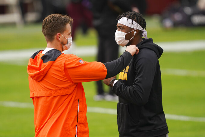 Cincinnati Bengals quarterback Joe Burrow (9) touches Washington Football Team quarterback Dwayne Haskins's sweater, right, as they talk on the field during pregame warm-ups before the start of an NFL football game Sunday, Nov. 22, 2020, in Landover. (AP Photo/Andrew Harnik)