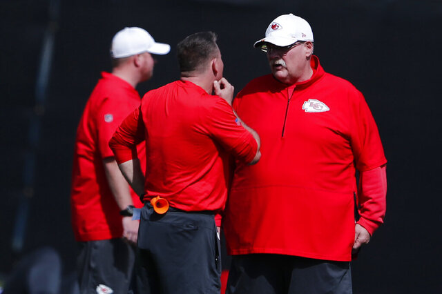 Kansas City Chiefs head coach Andy Reid, right, talks with others on the football field during practice on Thursday, Jan. 30, 2020, in Davie, Fla., for the NFL Super Bowl 54 football game. (AP Photo/Brynn Anderson)