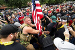 Joseph Oakman and fellow Proud Boys plant a flag in Tom McCall Waterfront Park during an