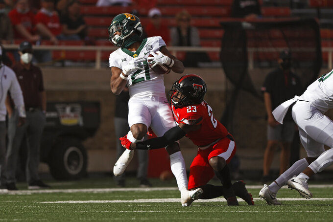 Texas Tech's DaMarcus Fields (23) tackles Baylor's Josh Fleeks (21) during the first half of an NCAA college football game Saturday, Nov. 14, 2020, in Lubbock, Texas. (Brad Tollefson/Lubbock Avalanche-Journal via AP)