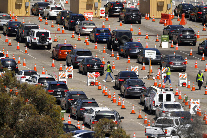 FILE - In this July 14, 2020 file photo, people wait in line for coronavirus testing at Dodger Stadium in Los Angeles. California health officials say the typical turn-around time for coronavirus tests has dropped so significantly that they soon expect to begin more widespread testing of the population to spot trends and outbreaks. (AP Photo/Mark J. Terrill, File)