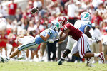 Tulane quarterback Michael Pratt (7) fumbles the ball while being tackled by Oklahoma defensive end Reggie Grimes (14) during NCAA college football game in Norman, Okla. on Saturday, Sept. 4, 2021. (Ian Maule/Tulsa World via AP)