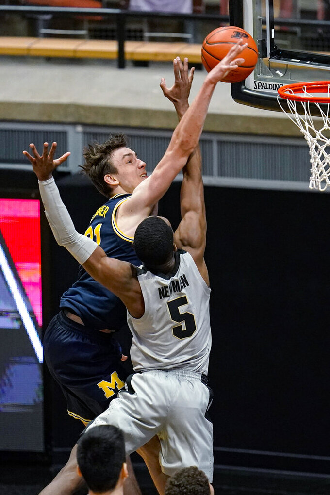 Purdue guard Brandon Newman (5) blocks the shot of Michigan guard Franz Wagner (21) during the second half of an NCAA college basketball game in West Lafayette, Ind., Friday, Jan. 22, 2021. (AP Photo/Michael Conroy)