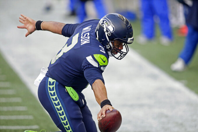 Seattle Seahawks quarterback Russell Wilson (3) reaches for the end zone as he runs for a touchdown against the Los Angeles Rams during the second half of an NFL football game, Sunday, Dec. 27, 2020, in Seattle. (AP Photo/Scott Eklund)