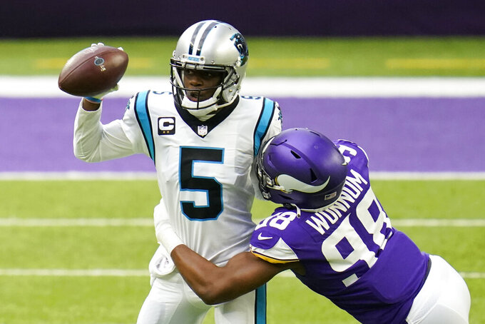 Carolina Panthers quarterback Teddy Bridgewater (5) tries to break a tackle by Minnesota Vikings defensive end D.J. Wonnum during the first half of an NFL football game, Sunday, Nov. 29, 2020, in Minneapolis. (AP Photo/Jim Mone)