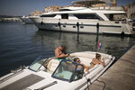 People enjoy the sun after docking at the port in Saint-Tropez, southern France, Saturday Aug 8, 2020. The glamorous French Riviera resort of Saint-Tropez is requiring face masks outdoors starting Saturday, threatening to sober the mood in a place renowned for high-end, free-wheeling summer beach parties. (AP Photo/Daniel Cole)