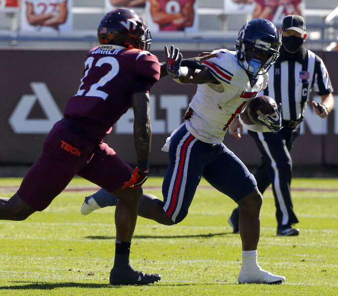Liberty quarterback Malik Willis, right, attempts to elude Virginia Tech's Chamarri Conner during the first half of an NCAA college football game, Saturday, Nov. 7 2020, in Blacksburg, Va. (Matt Gentry/The Roanoke Times via AP, Pool)