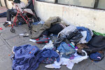 FILE - In this July 25, 2019, file photo, sleeping people, discarded clothes and used needles are seen on a street in the Tenderloin neighborhood in San Francisco. San Francisco has sued 28 alleged drug dealers who frequent a downtown neighborhood where broad daylight drug dealing and drug use is common to stop the flow of drugs. City Attorney Dennis Herrera said Thursday, Sept. 24, 2020, the suits are part of an effort to clean up the Tenderloin, which has seen the city's largest number of overdose deaths. (AP Photo/Janie Har, File)