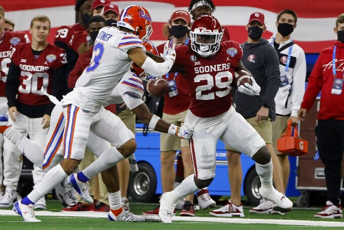 Florida defensive back Donovan Stiner attempts to stop Oklahoma running back Rhamondre Stevenson (29) after a long run during the first half of the Cotton Bowl NCAA college football game in Arlington, Texas, Wednesday, Dec. 30, 2020. (AP Photo/Michael Ainsworth)