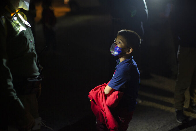 Davidson Jair, 7, answers questions from a U.S. Border Patrol agent at an intake site after he was smuggled on an inflatable raft across the Rio Grande river in Roma, Texas, Wednesday, March 24, 2021. Davidson traveled from El Salvador in the hope of reaching relatives living in the U.S. The Biden administration says that it's working to address the increase in migrants coming to the border. On Wednesday, President Joe Biden tapped Vice President Kamala Harris to lead the White House efforts at the U.S. southern border and work with Central American nations to address root causes of the migration. (AP Photo/Dario Lopez-Mills)