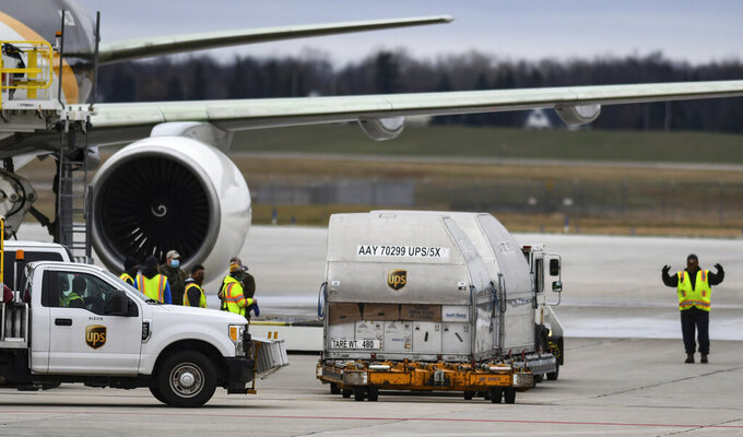 A UPS worker directs a vehicle transporting some of the first shipments of the Pfizer-BioNTech COVID-19 vaccines Sunday, Dec. 13, 2020, on the tarmac at Capital Region International Airport in Lansing, Mich., before they're loaded onto a UPS cargo jet to be distributed nationwide. (Matthew Dae Smith/Lansing State Journal via AP)