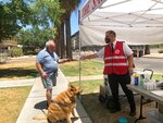 Salvation Army Maj. David Yardley, right, offers a bottle of water to a passerby and his dog outside the Salvation Army Phoenix downtown headquarters on Thursday, May 28, 2020, in Phoenix, Ariz. A heat relief station offering cold water and a cool place inside to rest out of the brutal sun will be open every day through Sunday while an excessive heat warning is in effect. (AP Photo/Anita Snow)