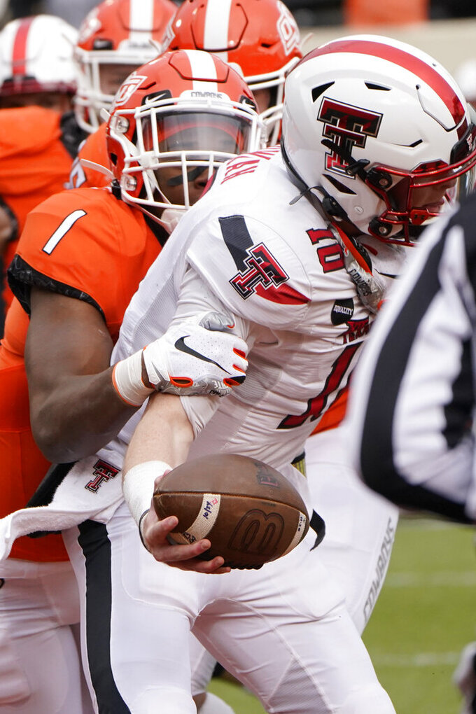 Oklahoma State linebacker Calvin Bundage (1) sacks Texas Tech quarterback Alan Bowman (10) in the second half of an NCAA college football game in Stillwater, Okla., Saturday, Nov. 28, 2020. (AP Photo/Sue Ogrocki)