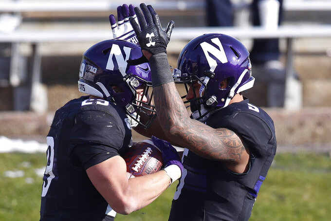 Northwestern's Evan Hull, left, celebrates his touchdown against Massachusetts with teammate Jace James during the second half of an NCAA college football game Saturday, Nov. 16, 2019, in Evanston, Ill. (AP Photo/Jim Young)