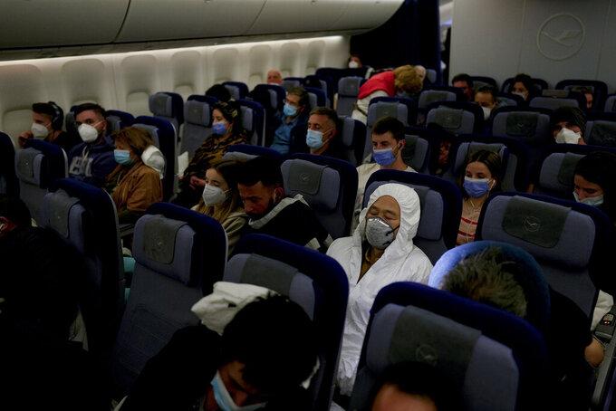 Passengers sit on a flight from Buenos Aires to Frankfurt, Germany, Saturday, July 17, 2021. (AP Photo/Natacha Pisarenko)