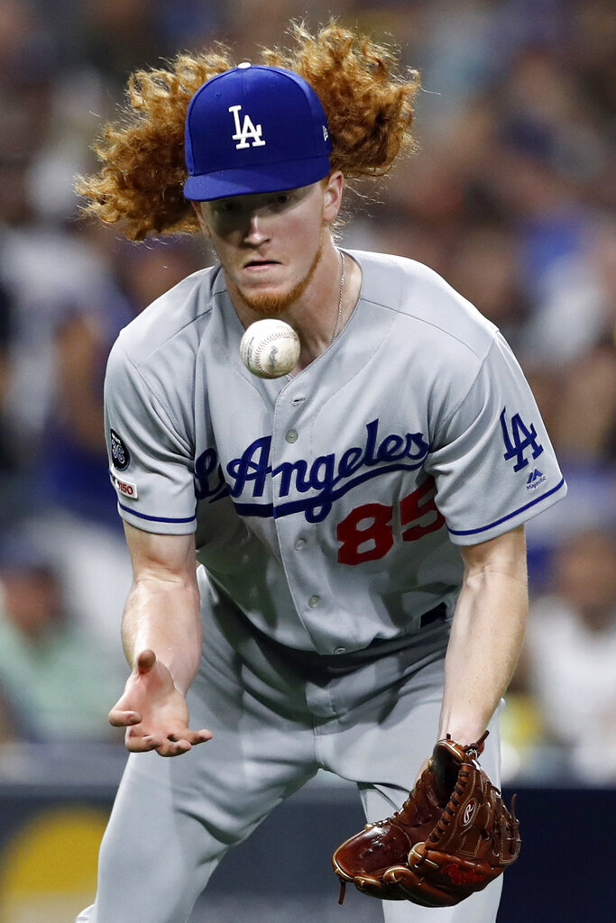 FILE - In this Aug. 26, 2019 file photo, Los Angeles Dodgers starting pitcher Dustin May bobbles a ground ball before throwing out San Diego Padres' Josh Naylor at first during the fourth inning of a baseball game in San Diego. May might be a part of the Dodgers' 2020 season. In what's become a familiar refrain, the Dodgers arrive at camp still looking for their first World Series championship since 1988. After losing in two straight World Series, they were ousted by Washington in five games in the NL Division Series last fall. (AP Photo/Gregory Bull, File)