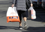 A shopper leaves a supermarket with goods in plastic bags in Christchurch, New Zealand, Friday, Aug. 10, 2018. New Zealand plans to ban disposable plastic shopping bags by next July as the nation tries to live up to its clean-and-green image. Prime Minister Jacinda Ardern said Friday that New Zealanders use hundreds of millions of the bags each year and that some of them end up polluting the precious coastal and marine environment. (AP Photo/Mark Baker)