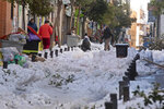 A man walks across a street covered with snow and ice in Madrid, Spain, Tuesday, Jan. 12, 2021. Much of Spain is struggling to return to normality three days after a 30-hour-long record snowfall that was then hardened by record-low temperatures, turning streets and roads into dangerous ice sheets in areas not used to extreme winters. Schools remain closed in Madrid and much of central Spain, with emergency and military crews still working to reopen roads, remove fallen trees, re-establish power lines and ensure the distribution of food and coronavirus vaccine. (AP Photo/Paul White)