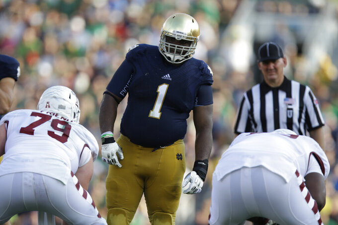 FILE - In this Saturday, Aug. 31, 2013, file photo, Notre Dame defensive lineman Louis Nix III (1) prepares to get into his defensive stance during the second half of an NCAA college football game against Temple in South Bend, Ind. Nix's mother, Stephanie Wingfield, says authorities told her that her son had died but they were unable to give her more information about his death. The Jacksonville Sheriff's Office said in a tweet Saturday, Feb. 27, 2021, that Nix was located, but didn't give any other details. (AP Photo/Michael Conroy, File)