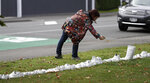 A woman photographs a memorial of 50 pairs of white shoes for the victims of Friday March 15 mass mosque shootings in front of a church in Christchurch, New Zealand, Tuesday, March 19, 2019.  Four days after Friday's attack, New Zealand's deadliest shooting in modern history, relatives were anxiously waiting for word on when they can bury their loved ones. (AP Photo/Mark Baker)