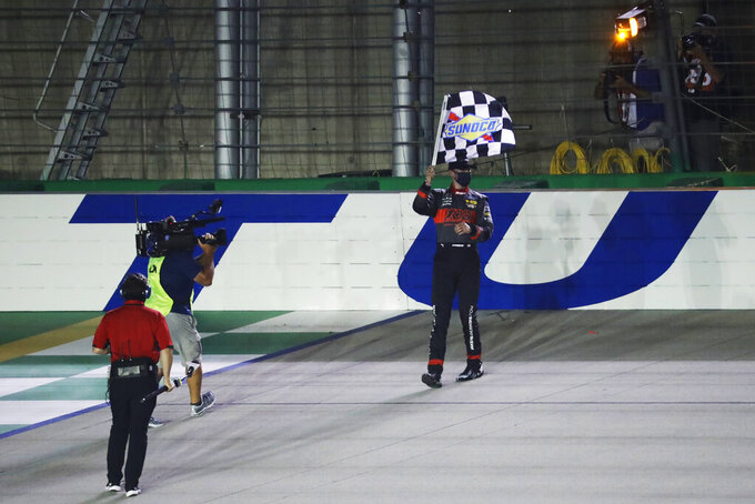 Austin Cindric waves the checkered flag after a NASCAR Xfinity Series auto race Thursday, July 9, 2020, in Sparta, Ky. (AP Photo/Mark Humphrey)