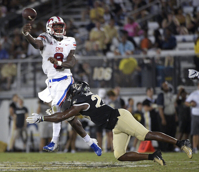 SMU quarterback William Brown (9) throws a pass as he is hit by Central Florida linebacker Shawn Burgess-Becker, right, during the second half of an NCAA college football game Saturday, Oct. 6, 2018, in Orlando, Fla. UCF won 48-20. (AP Photo/Phelan M. Ebenhack)