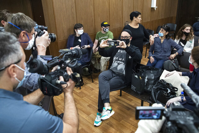 Russian theatre and film director Kirill Serebrennikov, centre, wearing a face mask with a portrait of Russian rock singer Viktor Tsoi, takes photos of the media prior to his hearing in a court in Moscow, Russia, Monday, June 22, 2020. Russian prosecutors on Monday demanded a six-year prison term for an acclaimed theater director accused of embezzling state funds, in case widely seen as politically motivated.  (AP Photo/Pavel Golovkin)