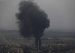 In this photo taken from the Turkish side of the border between Turkey and Syria, in Ceylanpinar, Sanliurfa province, southeastern Turkey, smoke billows from a target behind a mosque's minaret in Ras al-Ayn, Syria, during bombardment by Turkish forces, Wednesday, Oct. 16, 2019. Turkey's President Recep Tayyip Erdogan called Wednesday on Syrian Kurdish fighters to leave a designated border area in northeast Syria 'as of tonight' for Turkey to stop its military offensive, defying pressure on him to call a ceasefire and halt its incursion into Syria, now into its eighth day. (AP Photo/Lefteris Pitarakis)