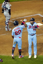 Minnesota Twins' Eddie Rosario, left, and Jake Cave celebrate Cave's two-run home run off Detroit Tigers pitcher Casey Mize during the fourth inning of a baseball game Wednesday, Sept. 23, 2020, in Minneapolis. (AP Photo/Jim Mone)