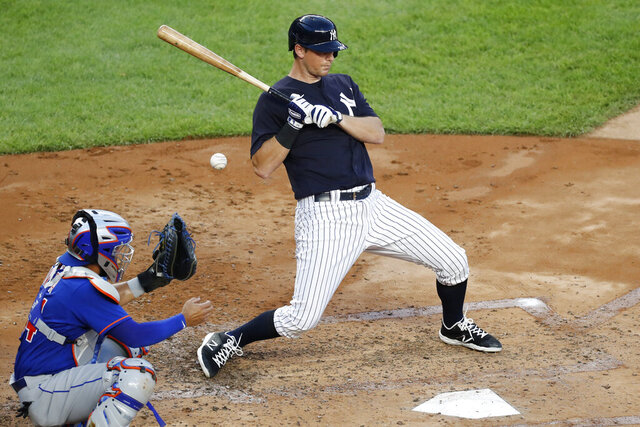 New York Yankees D.J. LeMahieu right, leans away from an inside pitch during the second inning of an exhibition game against the New York Mets, Sunday, July 19, 2020, at Yankee Stadium in New York. Mets catcher Rene Rivera is at left. It was LeMahieu's first appearance in a game since returning to the team following a positive coronavirus test. (AP Photo/Kathy Willens)