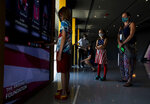 FILE - In this July 30, 2020, file photo, Madeleine McIlhargie, 8, sports a stars and stripe dress with her brother Ronan, 10, left, and her mother Elody McIlhargie, right, during the opening day of the U.S. Olympic and Paralympic Museum in Colorado Springs Colo. The $88 million, 60,000-square-foot museum and hall of fame, envisioned as a tribute to the nation's Olympic and Paralympic movements through interactive displays, media, exhibits, and artifacts. The museum took three years to build and is considered the most accessible and interactive museum in the United States. (Chancey Bush/The Gazette via AP, File)