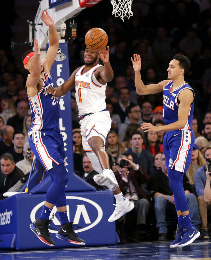 New York Knicks' Emmanuel Mudiay, center, passes between Philadelphia 76ers defenders during the first half of an NBA basketball game, Sunday, Jan. 13, 2019, in New York. (AP Photo/Seth Wenig)