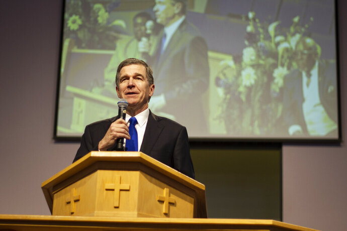FILE - In this July 14, 2019 file photo, Democratic Gov. Roy Cooper speaks at Mount Olive Missionary Baptist Church in Fayetteville about his desire to expand Medicaid health coverage to several hundred thousand lower-income North Carolinians in Fayetteville, N.C.    Cooper's leverage is now being tested in a budget stalemate, as he pressures Republican legislators to expand Medicaid. He vetoed the state budget last month in part because it failed to expand Medicaid to hundreds of thousands of people.  (Paul Woolverton/The Fayetteville Observer via AP)