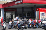 People on their scooters and motorcycles wait in queue for gasoline in Beirut, Lebanon, Friday in Beirut, Lebanon, Wednesday, June 23, 2021.  Lebanon is struggling amid a 20-month-old economic and financial crisis that has led to shortages of fuel and basic goods like baby formula, medicine and spare parts. The crisis is rooted in decades of corruption and mismanagement by a post-civil war political class. (AP Photo/Hussein Malla)