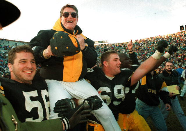 FILE - In this Nov. 20, 1993, file photo, Iowa football coach Hayden Fry is carried off the field after his team defeated Minnesota in an NCAA college football game, giving him his 200th career victory in Iowa City, Iowa. Fry, the Texan who revived Iowa football and became a Hawkeye State institution, died Tuesday, Dec. 17, 2019, after a long battle with cancer. He was 90. (AP Photo/Charlie Neibergall, File)
