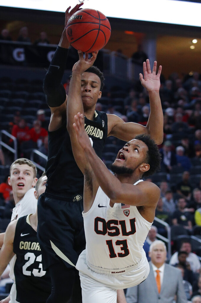 Colorado's Shane Gatling (0) guards Oregon State's Antoine Vernon (13) during the second half of an NCAA college basketball game in the quarterfinals of the Pac-12 men's tournament Thursday, March 14, 2019, in Las Vegas. (AP Photo/John Locher)