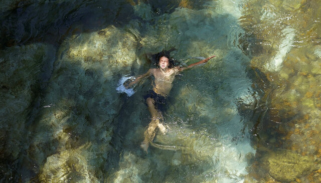 A boy swims in the cool waters of the Comal River as temperatures hit triple digits, Wednesday, Aug. 12, 2020, in New Braunfels, Texas. (AP Photo/Eric Gay)