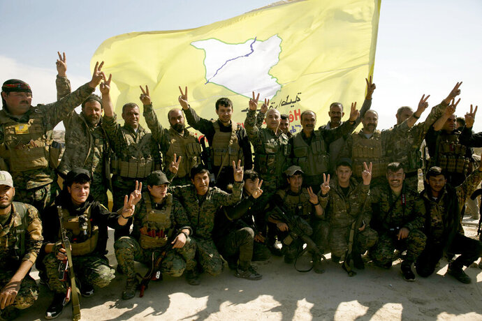 FILE - In this March 23, 2019 file photo, U.S.-backed Syrian Democratic Forces (SDF) fighters pose for a photo in Baghouz, Syria, after the SDF declared the area free of Islamic State militants. SDF defeated the IS in March but the Kurdish-led force is now facing protests by local Arab tribesmen in Deir el-Zour province. If the protests turn to an all-out uprising against the SDF it could be a blow to Washington as President Trump has plans to reduce America's military presence in Syria. (AP Photo/Maya Alleruzzo, File)