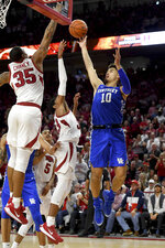 Kentucky guard Johnny Juzang (10) pulls up for a jump shot over Arkansas defenders Jimmy Whitt Jr. (33) and Reggie Chaney (35) during the second half of an NCAA college basketball game, Saturday, Jan. 18, 2020, in Fayetteville, Ark. (AP Photo/Michael Woods)