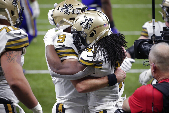 New Orleans Saints running back Alvin Kamara (41) hugs quarterback Drew Brees (9) after scoring his sixth touchdown of the game, tying the NFL record for most rushing touchdowns in a game, in the second half of an NFL football game against the Minnesota Vikings in New Orleans, Friday, Dec. 25, 2020. Drew Brees also set an NFL record as the first player to ever reach 80,000 yards passing. (AP Photo/Butch Dill)