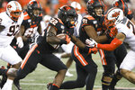 Oregon State running back Jermar Jefferson (22) tries to avoid Oklahoma State safety Malcolm Rodriguez (20) during the second half of an NCAA college football game in Corvallis, Ore., Friday, Aug. 30, 2019. Oklahoma State won 52-36. (AP Photo/Amanda Loman)