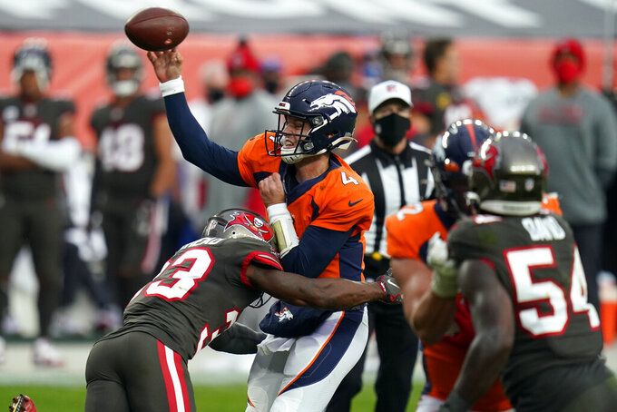 Denver Broncos quarterback Brett Rypien is hit by Tampa Bay Buccaneers free safety Jordan Whitehead as he throws a pass during the second half of an NFL football game Sunday, Sept. 27, 2020, in Denver. (AP Photo/Jack Dempsey)