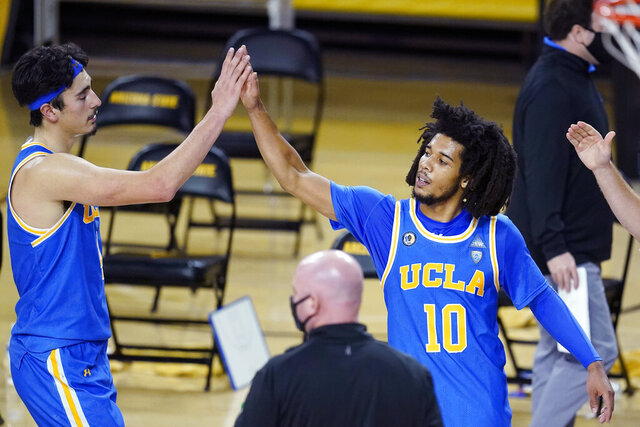UCLA guard Tyger Campbell (10) gives a high-five to Jaime Jaquez Jr. as time expires in overtime of the team's NCAA college basketball game against Arizona State on Thursday, Jan. 7, 2021, in Tempe, Ariz. UCLA won 81-75. (AP Photo/Ross D. Franklin)