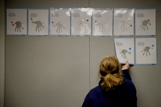FILE - In this May 12, 2020, file photo, a teacher removes students' artwork from a bulletin board as she packs the art in her kindergarten classroom at an elementary school in Olathe, Kan. The coronavirus is proving ruinous to state budgets, forcing many governments to consider once-unthinkable cuts to schools, universities, health care programs and a wide array of other basic functions. (AP Photo/Charlie Riedel, File)