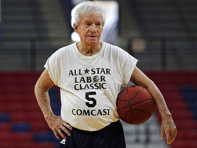 Jack Scheuer, who ran Wednesday noon pickup games at the Palestra for four decades, waits to start a game Jan. 21, 2015, in Philadelphia. Scheuer, the go-to guy at courtside, on the field and in the press box, who covered Philadelphia sports from the days of Wilt Chamberlain to Bryce Harper for The Associated Press and other outlets, died Friday, Oct. 16, 2020. He was 88. (David Maialetti/The Philadelphia Inquirer via AP)