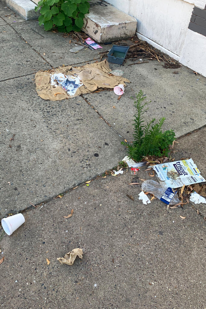 Trash rests on a street Tuesday, July 28, 2020, in the Kensington neighborhood of Philadelphia. The COVID-19 pandemic has frustrated efforts to keep Philadelphia's streets clear of garbage this summer. People are staying home and generating more garbage, but the sanitation department has been shorthanded and workers have fallen behind picking up household trash and recyclables. (Kara Kneidl via AP)