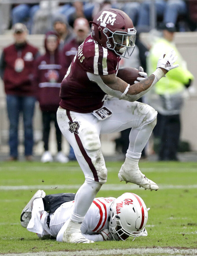 Texas A&M running back Trayveon Williams (5) steps over Mississippi Rebels defensive back Vernon Dasher while rushing for a gain during the second half of an NCAA college football game Saturday, Nov. 10, 2018, in College Station, Texas. Texas A&M won 38-24. (AP Photo/David J. Phillip)